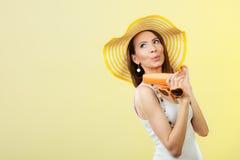 Η γυναίκα στο θερινό καπέλο κρατά sunscreen γυαλιών ηλίου το λοσιόν Στοκ φωτογραφία με δικαίωμα ελεύθερης χρήσης