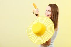 Η γυναίκα στο θερινό καπέλο κρατά sunscreen γυαλιών ηλίου το λοσιόν Στοκ Φωτογραφία