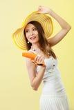 Η γυναίκα στο θερινό καπέλο κρατά sunscreen γυαλιών ηλίου το λοσιόν Στοκ Εικόνες