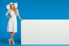 Η γυναίκα στο θερινό φόρεμα, το καπέλο ήλιων και τα υψηλά τακούνια θέτει με το άσπρο έμβλημα στοκ φωτογραφία