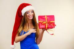 Η γυναίκα στο καπέλο Άγιου Βασίλη κρατά το κιβώτιο δώρων στενός κόκκινος χρόνος Χριστουγέννων ανασκόπησης επάνω Στοκ εικόνες με δικαίωμα ελεύθερης χρήσης