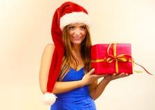 Η γυναίκα στο καπέλο Άγιου Βασίλη κρατά το κιβώτιο δώρων στενός κόκκινος χρόνος Χριστουγέννων ανασκόπησης επάνω Στοκ φωτογραφίες με δικαίωμα ελεύθερης χρήσης