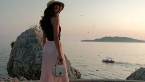 Η γυναίκα στο καπέλο και την πτυχωμένη μακριά φούστα περπατά κατά μήκος της νότιας ακτής φιλμ μικρού μήκους