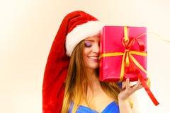 Η γυναίκα στο καπέλο Άγιου Βασίλη κρατά το κιβώτιο δώρων στενός κόκκινος χρόνος Χριστουγέννων ανασκόπησης επάνω Στοκ φωτογραφία με δικαίωμα ελεύθερης χρήσης