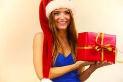 Η γυναίκα στο καπέλο Άγιου Βασίλη κρατά το κιβώτιο δώρων στενός κόκκινος χρόνος Χριστουγέννων ανασκόπησης επάνω Στοκ Εικόνες