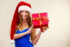 Η γυναίκα στο καπέλο Άγιου Βασίλη κρατά το κιβώτιο δώρων στενός κόκκινος χρόνος Χριστουγέννων ανασκόπησης επάνω Στοκ Φωτογραφίες
