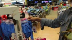 Η γυναίκα στο κατάστημα επιλέγει τη μόδα μαγιό φιλμ μικρού μήκους