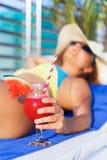 Η γυναίκα στο καταφερτζή χυμού καπέλων πίνει την πισίνα κοκτέιλ πλησίον Στοκ Εικόνα