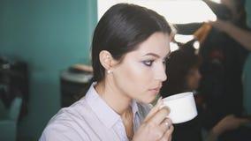 Η γυναίκα στο κομμωτήριο πίνει τον καφέ Στοκ Εικόνα