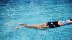 Η γυναίκα στο μαγιό επιπλέει και χαλαρώνοντας σε ένα μπλε νερό λιμνών και κάνοντας τον παφλασμό νερού με τα πόδια της φιλμ μικρού μήκους
