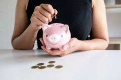 Η γυναίκα στο μαύρο πουκάμισο διδάσκει τις εξαρτήσεις στην τοποθέτηση του νομίσματος στη ρόδινη τράπεζα Piggy στοκ φωτογραφία με δικαίωμα ελεύθερης χρήσης