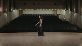 Η γυναίκα στο μαύρο φόρεμα χορεύει στο στάδιο στην κενή αίθουσα φιλμ μικρού μήκους