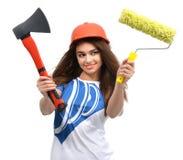 Η γυναίκα στο πορτοκαλί καπέλο ασφάλειας κατασκευής παρουσιάζει βούρτσα χρωμάτων τσεκουριών Στοκ Εικόνα