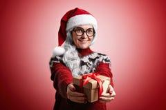 Η γυναίκα στο πουλόβερ Χριστουγέννων και το καπέλο Santa με παρουσιάζει Στοκ Φωτογραφία