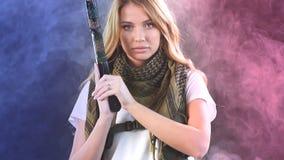 Η γυναίκα στο προστατευτικό τεθωρακισμένο κρατά το πυροβόλο όπλο στα χέρια Στρατός, αφιέρωση, τεχνολογία φιλμ μικρού μήκους