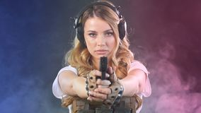 Η γυναίκα στο προστατευτικό τεθωρακισμένο κρατά το πυροβόλο όπλο στα χέρια Στρατός, αφιέρωση, τεχνολογία o απόθεμα βίντεο