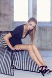 Η γυναίκα στο σκοτεινό φόρεμα κάθεται στην καλλιτεχνική μαύρη καρέκλα Στοκ Φωτογραφία