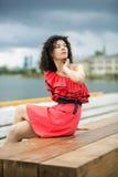 Η γυναίκα στο συμπαθητικό φόρεμα κάθεται στον πάγκο Στοκ Φωτογραφία