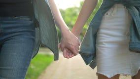 Η γυναίκα στο τζιν παντελόνι και ένα κορίτσι σε μια άσπρη φούστα τζιν πηγαίνουν εκμετάλλευση παραδίδουν το πάρκο E φιλμ μικρού μήκους