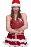 Η γυναίκα στο φόρεμα Άγιου Βασίλη και τα δώρα τοποθετούν σε σάκκο στοκ εικόνα