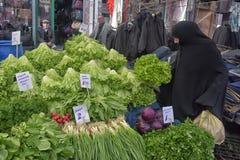 Η γυναίκα στο hijab αγοράζει τα λαχανικά στην αγορά Στοκ Εικόνες