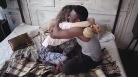 Η γυναίκα στρίβει τη σφαίρα, επιλογές ανδρών η θέση στο ταξίδι Το πολυφυλετικό ζεύγος στις πυτζάμες χαίρεται, αγκαλιάζει και φιλά Στοκ Εικόνες
