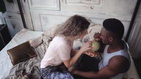Η γυναίκα στρίβει τη σφαίρα, επιλογές ανδρών η θέση στο ταξίδι Το πολυφυλετικό ζεύγος στις πυτζάμες χαίρεται, αγκαλιάζει και φιλά Στοκ Φωτογραφία