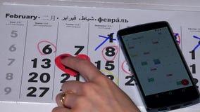 Η γυναίκα συγκρίνει το ημερολόγιο εγγράφου και το αρρενωπό ημερολόγιο συσκευών της απόθεμα βίντεο