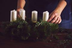 Η γυναίκα συνδέει τον κάτοχο κεριών σε ένα στεφάνι Χριστουγέννων στοκ φωτογραφίες με δικαίωμα ελεύθερης χρήσης