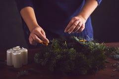 Η γυναίκα συνδέει τον κάτοχο κεριών σε ένα στεφάνι Χριστουγέννων στοκ εικόνες