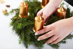 Η γυναίκα συνδέει το κερί σε ένα στεφάνι Χριστουγέννων στοκ φωτογραφίες με δικαίωμα ελεύθερης χρήσης