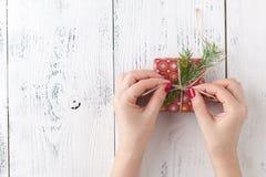 Η γυναίκα συσκευάζει τα δώρα Χριστουγέννων Κόκκινα κιβώτια δώρων Χριστουγέννων Στοκ Εικόνες