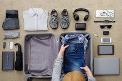 Η γυναίκα συλλέγει μια βαλίτσα για το ταξίδι και τον ελεύθερο χρόνο στοκ εικόνες με δικαίωμα ελεύθερης χρήσης