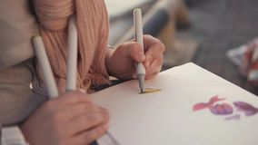 Η γυναίκα σύρει τα floral σχέδια σε ένα sketchbook, καθμένος σε έναν κήπο, κινηματογράφηση σε πρώτο πλάνο απόθεμα βίντεο