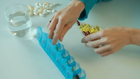 Η γυναίκα ταξινομεί τις θρεπτικές βιταμίνες στο μπλε κιβώτιο ταμπλετών στην εβδομάδα φιλμ μικρού μήκους