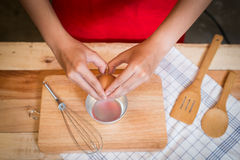 Η γυναίκα τα αυγά για το μαγείρεμα στον ξύλινο πίνακα Στοκ Φωτογραφία