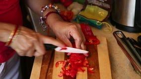 Η γυναίκα τεμαχίζει το κόκκινο πιπέρι απόθεμα βίντεο