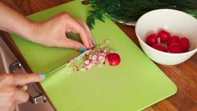 Η γυναίκα τεμαχίζει το φρέσκο ραδίκι στην κουζίνα στον ξύλινο πίνακα φιλμ μικρού μήκους