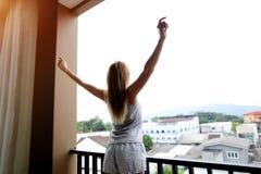 Η γυναίκα τεντώνει μετά από τον ύπνο στο μπαλκόνι απολαμβάνοντας το ταξίδι στοκ εικόνα με δικαίωμα ελεύθερης χρήσης