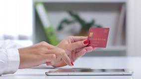 Η γυναίκα τελειώνει επάνω την πληρωμή on-line αγορών με μια κάρτα μέσω της ταμπλέτας κλείστε επάνω απόθεμα βίντεο