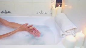 Η γυναίκα την πλένει παραδίδει ένα λουτρό με τον αφρό φιλμ μικρού μήκους