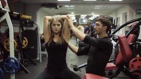 Η γυναίκα τινάζει τα triceps της με τους αλτήρες με την προγύμναση απόθεμα βίντεο