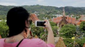 Η γυναίκα τουριστών παίρνει τις εικόνες των τηλεφωνικών θεών στην Ταϊλάνδη το καλοκαίρι απόθεμα βίντεο