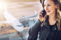 Η γυναίκα τουριστών στο καπέλο και με το σακίδιο πλάτης στέκεται στον αερολιμένα, που μιλά στο τηλέφωνο κυττάρων Στο άσπρο αεροπλ Στοκ φωτογραφία με δικαίωμα ελεύθερης χρήσης