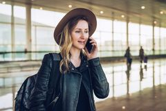 Η γυναίκα τουριστών στο καπέλο και με το σακίδιο πλάτης στέκεται στον αερολιμένα και μιλά στο τηλέφωνο κυττάρων Στάσεις κοριτσιών Στοκ Εικόνες