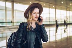 Η γυναίκα τουριστών στο καπέλο και με το σακίδιο πλάτης στέκεται στον αερολιμένα και μιλά στο τηλέφωνο κυττάρων Στάσεις κοριτσιών Στοκ εικόνες με δικαίωμα ελεύθερης χρήσης