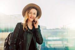 Η γυναίκα τουριστών στο καπέλο με το σακίδιο πλάτης στέκεται στον αερολιμένα και μιλά στο τηλέφωνο κυττάρων Στάσεις κοριτσιών, ψη Στοκ Εικόνα