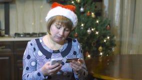 Η γυναίκα του Μεσαίωνα με το καπέλο Χριστουγέννων κάνει μια αγορά από ένα κινητό τηλέφωνο από την πιστωτική κάρτα φιλμ μικρού μήκους