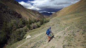 Η γυναίκα του Yong με το σακίδιο πλάτης αναρριχείται επάνω στο βουνό πετρών Υπάρχει όμορφοι βουνό και ουρανός με το σύννεφο στο υ απόθεμα βίντεο