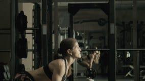 Η γυναίκα το weightlifter ανυψώνει έναν φραγμό απόθεμα βίντεο